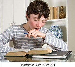 Young teenager boy studying a boring lesson