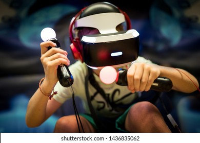 Young teenager boy using a Virtual reality headset with goggles and hands motion controllers in playing game zone. Modern technologies concept image.