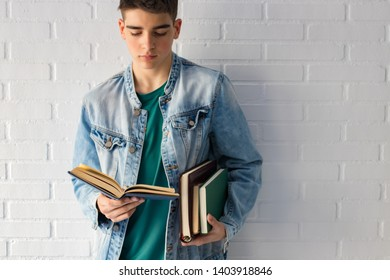 young teenager or fashion student with books supported on the wall