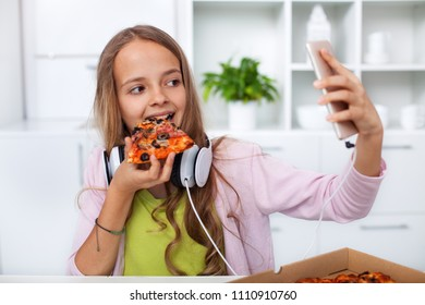 Young teenager girl eating pizza in the kitchen - making a selfie with her smartphone