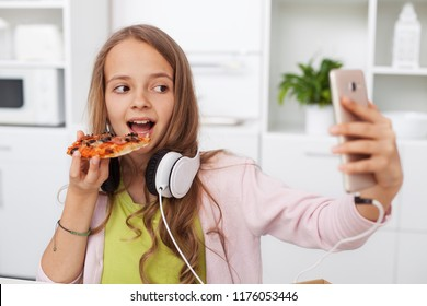 Young teenager girl eating pizza in the kitchen - searching for the perfect frame for a selfie, using her smartphone