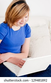 young teenager girl with laptop smilig ssitting on couch
