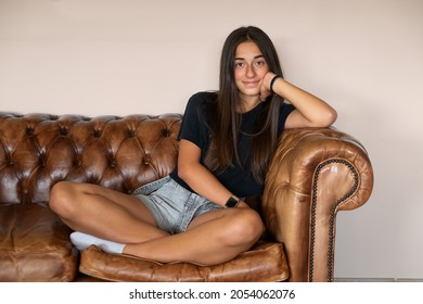 Young teenager girl on luxury leather sofa looking at camera. Quite and relaxing indoor portrait