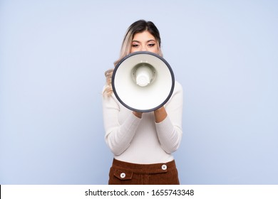Young teenager girl over isolated blue background shouting through a megaphone