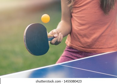 Young teenager girl playing ping pong. She holds a ball and a racket in her hands. Playing table tennis outdoors in the yard