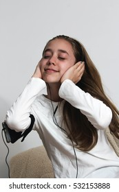 Young teenager girl with smart phone and wearing earphone listening music and talking