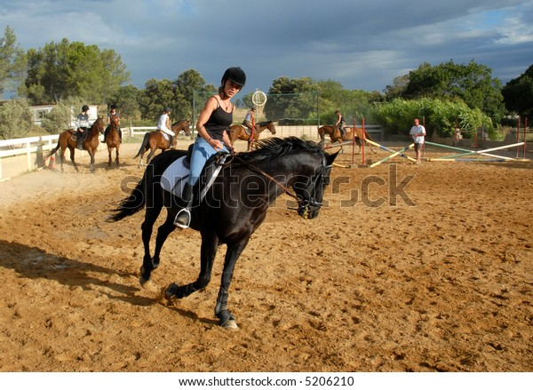 young teenager and her black horse in a training of jumping competition