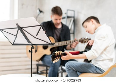 Young teenager and his older brother learining to play acoustic guitar together