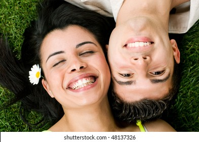 Young teenager latin couple have fun in a meadow