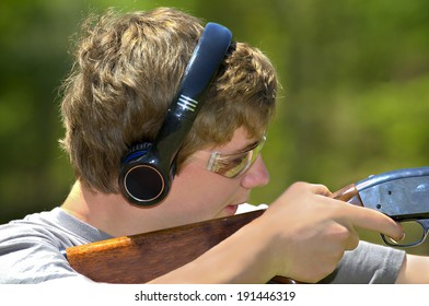 A young teenager learning to shoot targets with a shotgun.