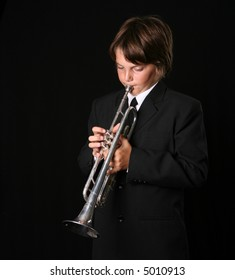Young Teenager Playing the Trumpet on Black