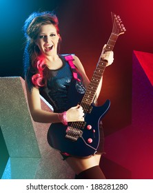 Young teenager rock star singing and playing electric guitar on stage.