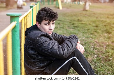 A young teenager sits on the grass and smiles, he is glad that the fall has started, it is no longer hot and he can play outdoor sports. The guy reconciled with his parents so he has a good mood