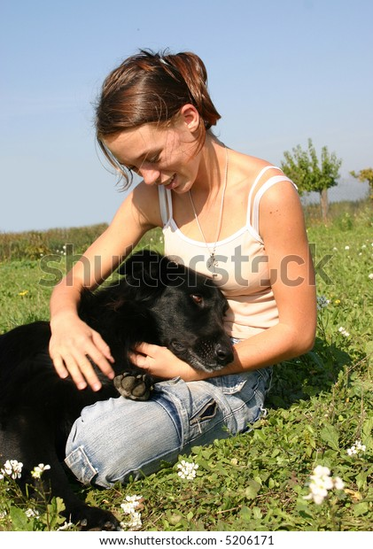 young teenager sitting in a meadow with her best friend black dog