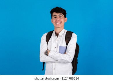 Young teenager standing on the middle of the portrait crossed arms wearing backpack on a blue background.