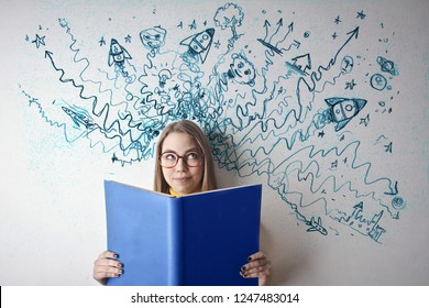 Young teenager studying with a big blue book.