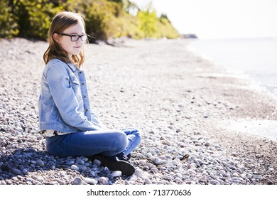young teenager is wearing jeans, posing outdoors on the beach