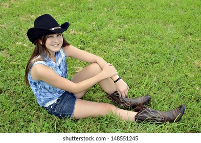 A young teenager with western hat and boots sitting in the grass smiling.