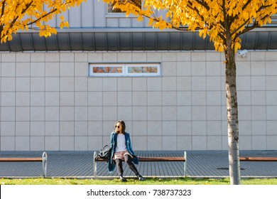 Young teenager woman sitting alone on the bench in sunny autumn day over modern building background. Life style, seasons and relax concept.