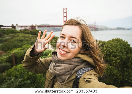 A young teenager woman smiling and making selfie self-portrait near Golden Gate Bridge in San Francisco when travel across California, USA