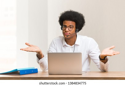 Young telemarketer black man doubting and shrugging shoulders