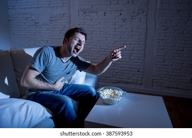 young television addict man sitting on home sofa watching TV and eating popcorn laughing crazy enjoying comedy movie or funny sitcom at night