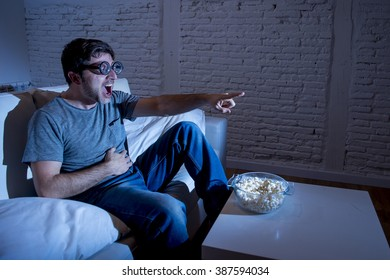 young television addict man sitting on home sofa watching TV and eating popcorn wearing funny nerd and geek glasses laughing crazy enjoying comedy movie or sitcom at night