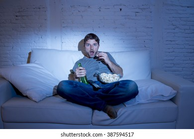 young television addict man sitting on home sofa watching TV eating popcorn and drinking beer bottle looking mesmerized enjoying movie sitcom or live sport at night