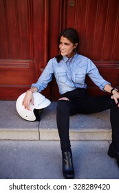 Young and tempting female sitting on the steps with her motorbike helmet, female rider is relaxing after fast driving. Street style look with young hipster girl posing in urban setting. Smiling woman