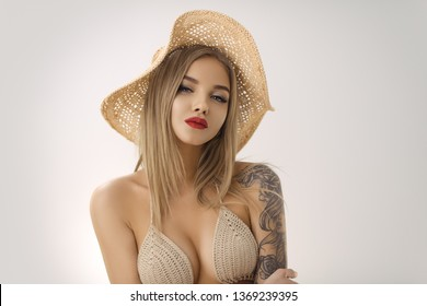 Young tender blonde woman posing in fashionable knit swimsuit and hat. Stylish sensual girl with perfect makeup an ideal body. Studio shot close up portrait. Attractive female in a sexy bikini looking