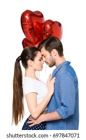 young tender couple hugging and holding heart shaped balloons, isolated on white