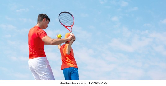 A young tennis coach or instructor teaches a child tennis player service techniques. Kids tennis on the court. Tennis school or club. Blue sky background. Banner size. Copy space for text.