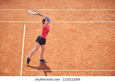 Young tennis player hitting ball on a sunny day