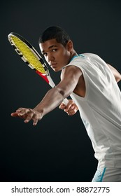 Young tennis player with racket ready to hit a tennis ball