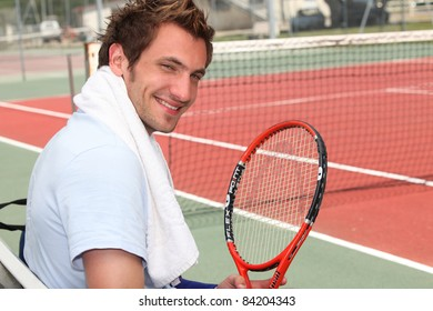 Young tennis player sitting on the court sidelines