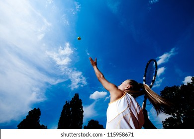 Young tennis woman in a white tennis dress developing ball service