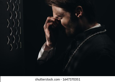young tense catholic priest touching face with closed eyes near confessional grille in dark with rays of light