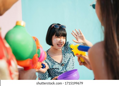 Young thai bob hairstyle pretty cute girl enjoy Songkran day with people. Woman reaching hand to touch people cheek with wet flour, powder. white clay in purple water bowl.