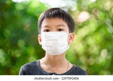 Young Thai boy put a mask on his face to protect a dust in a pollution air.