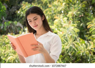 Young Thai girl reading a book outdoors