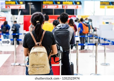 Young Thai woman  standing in queue waiting to check-in registration before flight. Back view.