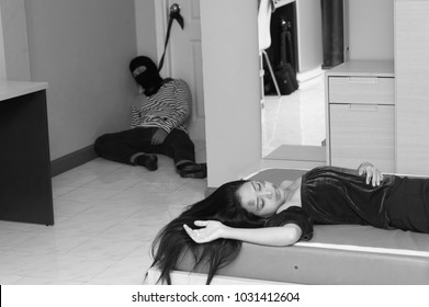 Young Thief /robber sleeping in front of the door and good looking and long hair young woman lying on the bed in condo and Expected to be taken hostage. Crime city and Security concept.