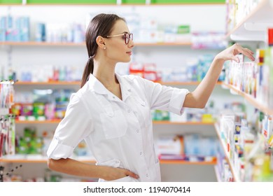A young thin brown-haired girl with glasses,dressed in a lab coat, takes some medicines from the shelf in a pharmacy. The girl's profile is shown.