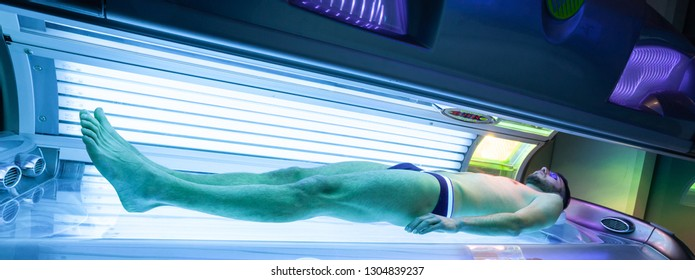 Young Thin Man At Solarium In Beauty Salon. Full tanning bed.