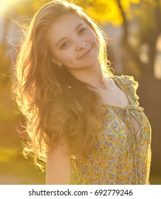 A young thin, slender girl with light long hair and dimples on her cheeks stands at sunset in the sunlight and smiles