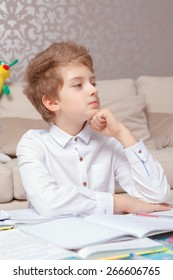 Young thinker. Small schoolboy thoughtfully holds his chin with a hand sitting by the table and doing tasks