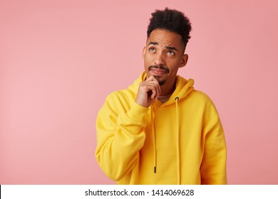 Young thinking african american guy in yellow hoodie, looks up and touches chin, stands over pink background with copy space.