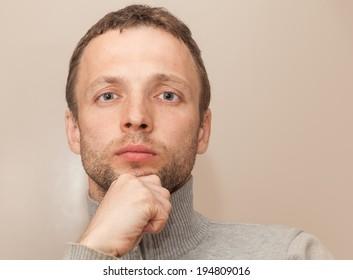 Young thinking Caucasian Man closeup studio portrait