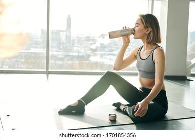 Joven sedienta en el uso activo de agua potable o té después del entrenamiento mientras se sienta en el tatami contra una gran ventana en el gimnasio o centro de ocio