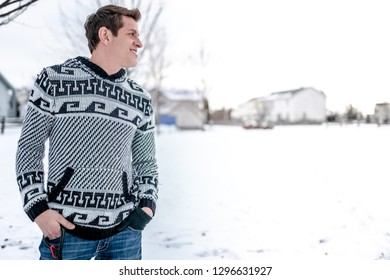 A young thirty year old gentleman standing in the snow with his hands in his blue jeans wearing a black and white patterned sweater while looking to his side towards open grass area covered in snow.
